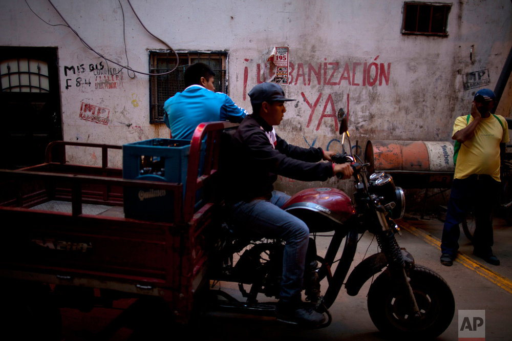 """In this May 2, 2017 photo, a motorcyclist drives past graffiti that reads in Spanish: """"Urbanize now!"""" in the Villa 31 slum in Buenos Aires, Argentina. A program by the Buenos Aires government aims to better integrate Villa 31 into the fabric of the city by offering its residents improved homes, credit to buy land, sewage, running water, and a connection to the power grid by 2020. (AP Photo/Natacha Pisarenko)"""