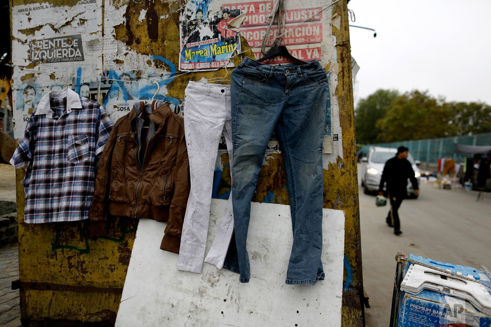 In this April 25, 2017 photo, clothing hangs for sale in the Villa 31 slum in Buenos Aires, Argentina. Villa 31 is one of the oldest, dating back to the 1930s, and one of the best-known because of its central location near the business district and the elegant French-inspired buildings of the Recoleta neighborhood. (AP Photo/Natacha Pisarenko)