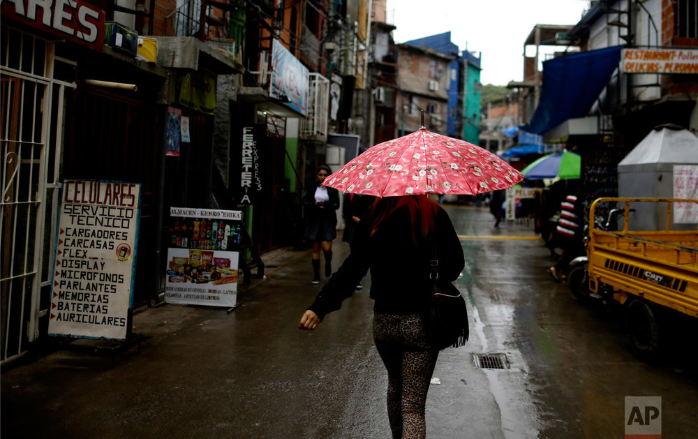In this April 25, 2017 photo, a woman walks through the Villa 31 slum on a rainy day in Buenos Aires, Argentina. The Buenos Aires government started a plan of urbanization and integration at the 31 slum, the oldest in the city. (AP Photo/Natacha Pisarenko)