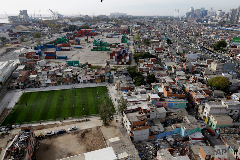 This May 5, 2017 photo shows an overhead view of the Villa 31 slum, featuring a soccer field, in Buenos Aires, Argentina. Sitting next to the most sophisticated neighborhood of Buenos Aires, the sprawling Villa 31 slum is about to get a serious face lift. (AP Photo/Natacha Pisarenko)