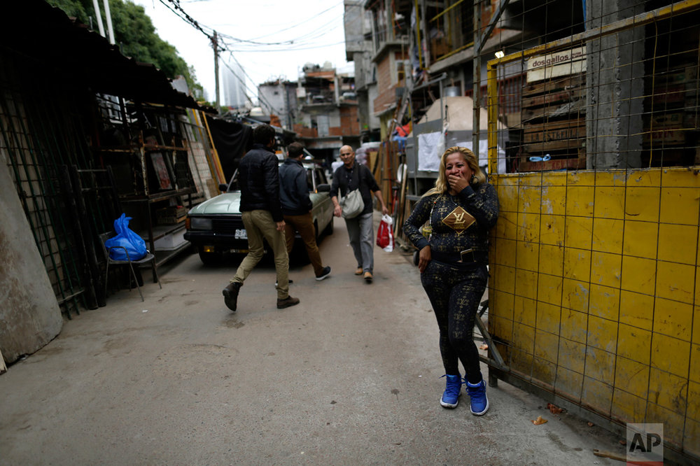 """In this April 25, 2017, a woman reacts to teasing by her neighbors calling her """"linda"""" or pretty, as she poses for a photo during a media tour in Villa 31 slum in Buenos Aires, Argentina. A program by the Buenos Aires government aims to better integrate Villa 31 into the fabric of the city by offering its residents improved homes, credit to buy land, sewage, running water, and a connection to the power grid by 2020. There are also plans to open a bank branch, schools and even a McDonald's restaurant in Villa 31. (AP Photo/Natacha Pisarenko)"""