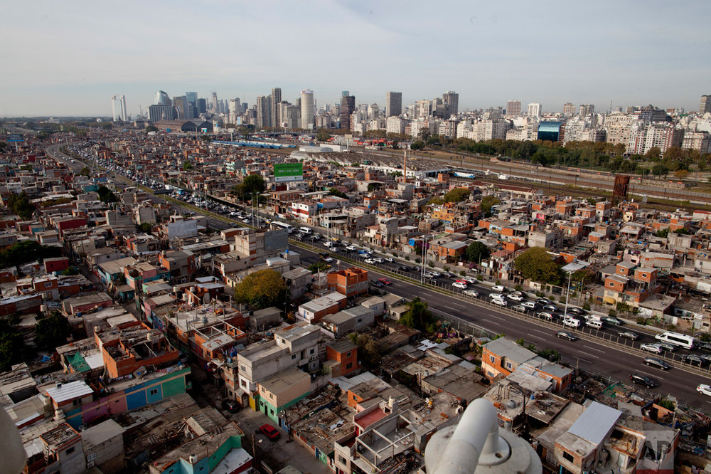 This May 5, 2017 photo shows a highway cutting through the Villa 31 slum in Buenos Aires, Argentina. The government says about 30 percent of Argentines live in poverty, unable to afford a basic basket of goods. Many of the poor live in the villas. (AP Photo/Natacha Pisarenko)