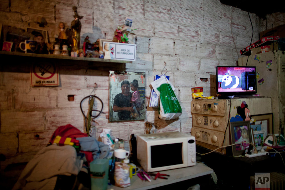 In this May 2, 2017 photo, Miguel Angel Molina and his granddaughter Zoe pose for a portrait, reflected in a mirror hanging on their wall in the Villa 31 slum in Buenos Aires, Argentina. His family of four shares two old mattresses and water leaks through the shack's zinc roof when it rains. The dirt floor is covered by a dusty carpet, and clothing and other belongings pile up in the corners. After two decades living like this, Molina hopes things are about to get better with a city improvement program that includes a connection to the power grid by 2020. (AP Photo/Natacha Pisarenko)