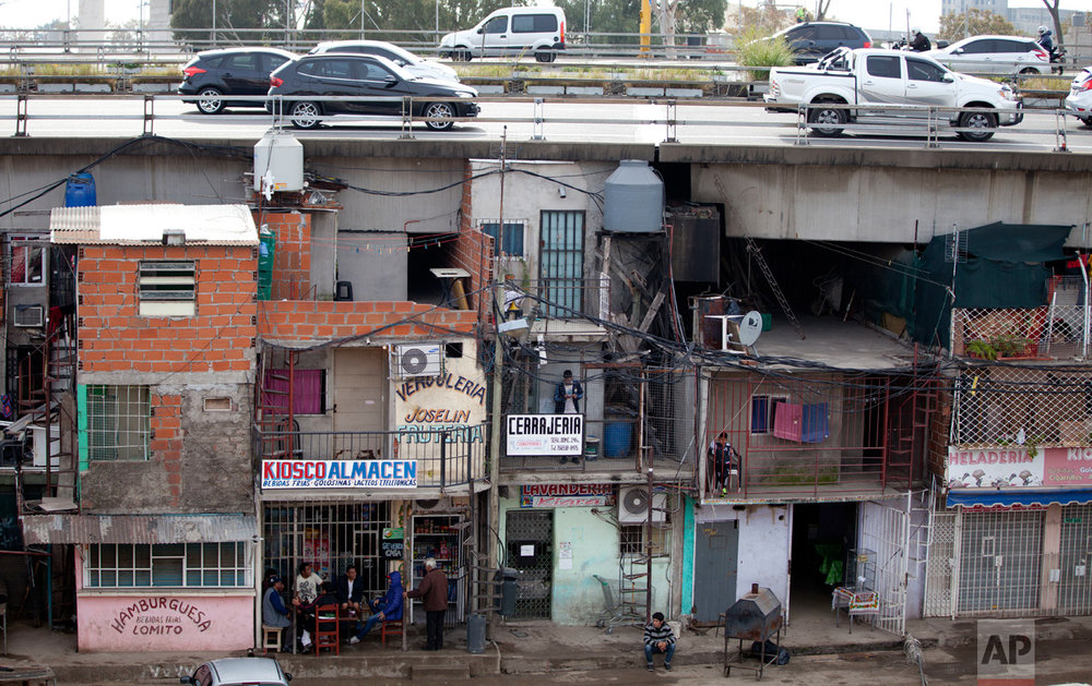 In this May 5, 2017 photo, cars drive on a highway over the Villa 31 slum in Buenos Aires, Argentina. The $320 million integration plan for Villa 31, which is being financed by the World Bank and the Inter-American Development Bank, also seeks to resettle families living beneath an elevated highway into 1,350 new homes.(AP Photo/Natacha Pisarenko)