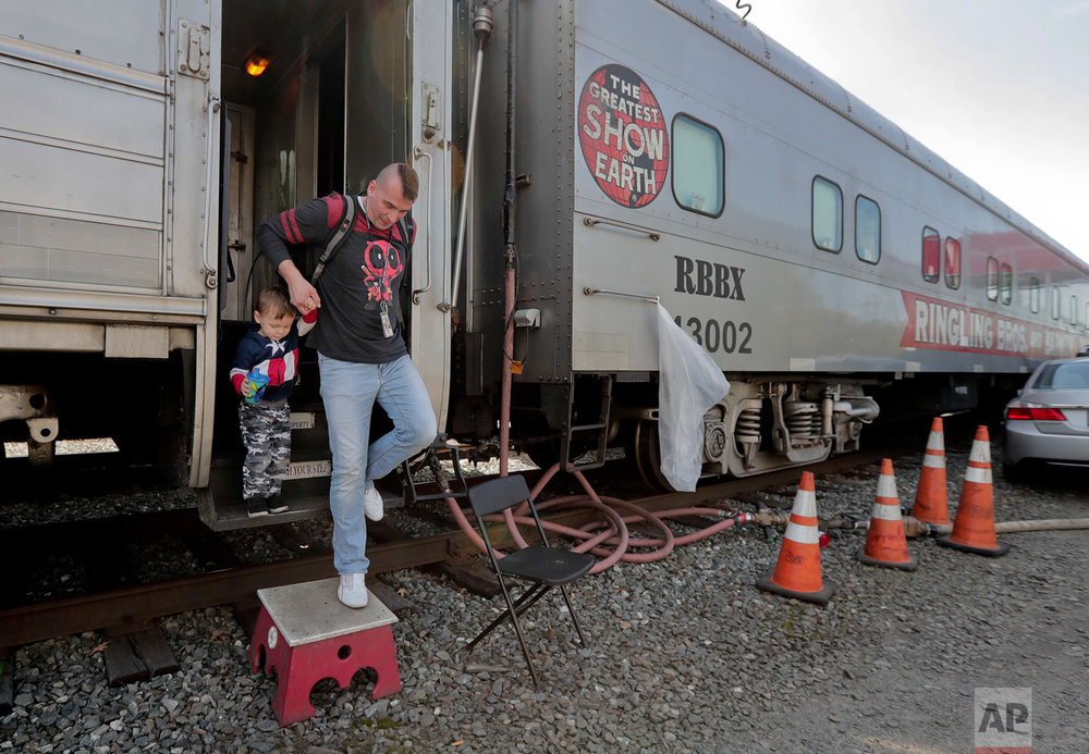 "Boss clown Sandor Eke helps his 2-year-old son. Michael Eke step off the Ringling Bros. circus red unit's traveling train parked in a rail yard as they head to the arena for a show, Thursday, May 4, 2017, in Providence, R.I. Someday, he plans to teach his son juggling and other circus skills, but Eke knows he may never join the circus. Eke's wife, a former circus aerialist, has already established their new home in Las Vegas. When the circus closes, Eke hopes to get a job as a ""flair"" bartender there, doing tricks like juggling bottles, but he wonders how life will change. ""My normal life is this. My normal life is going on the train, going every week to a different city. It's crazy how much I love circus,"" Eke says. (AP Photo/Julie Jacobson)"