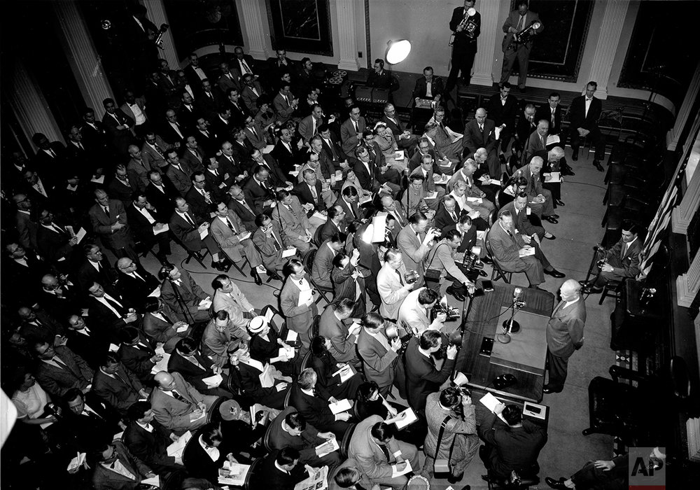 This aerial photo shows U.S. President Dwight D. Eisenhower standing behind a desk as he faces reporters and photographers at a news conference in the auditorium of the Executive Offices Building, across the street from the White House, in Washington, D.C., Feb. 25, 1953. This is the president's second news conference since taking office.  (AP Photo)