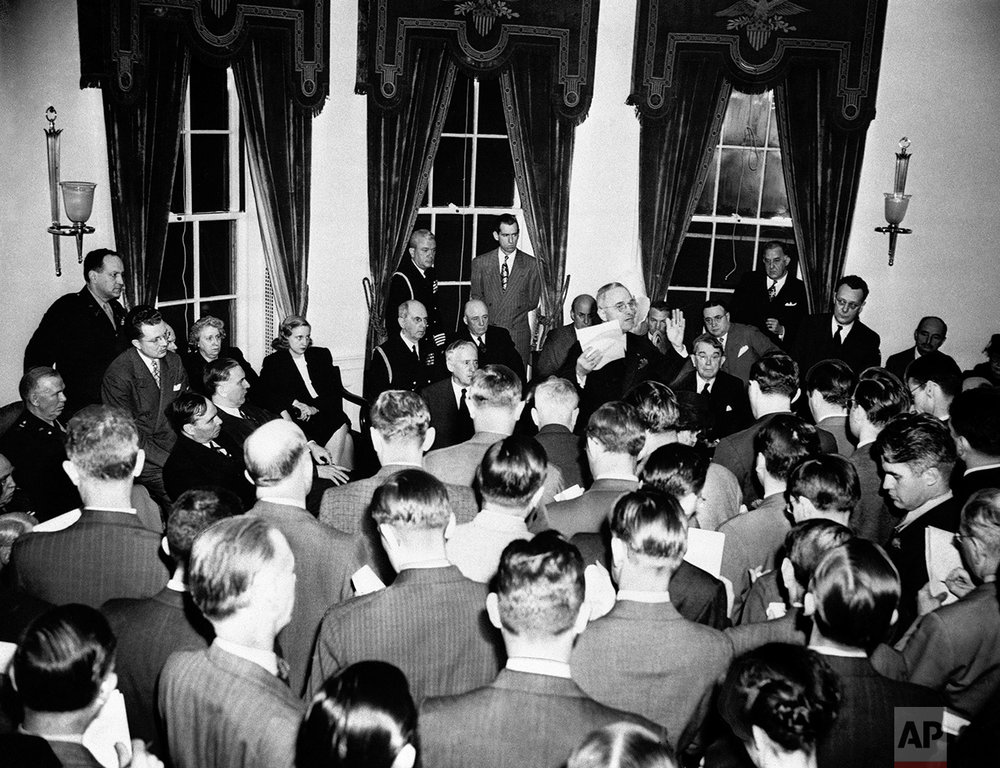 President Harry S. Truman (right center), gestures as he tells newsmen details of surrender of Germany during press conference at the White House in Washington, May 8, 1945 attended by 123 reporters. (AP Photo)