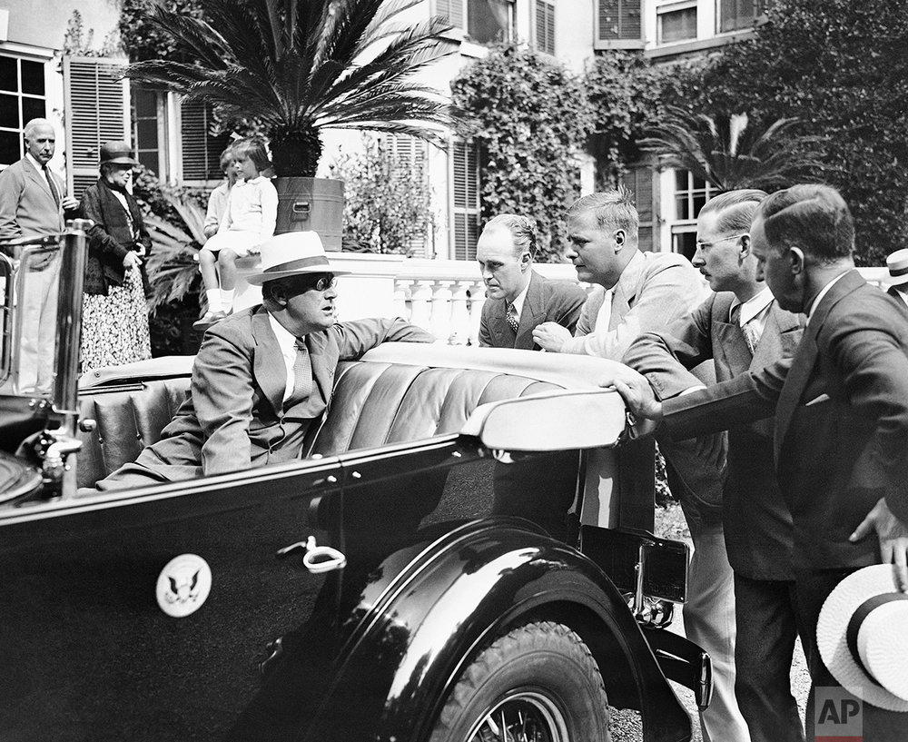 President Franklin D. Roosevelt speaks to reporters on his arrival at Hyde Park, N.Y., Aug. 20, 1933, to resume his vacation.  (AP Photo)