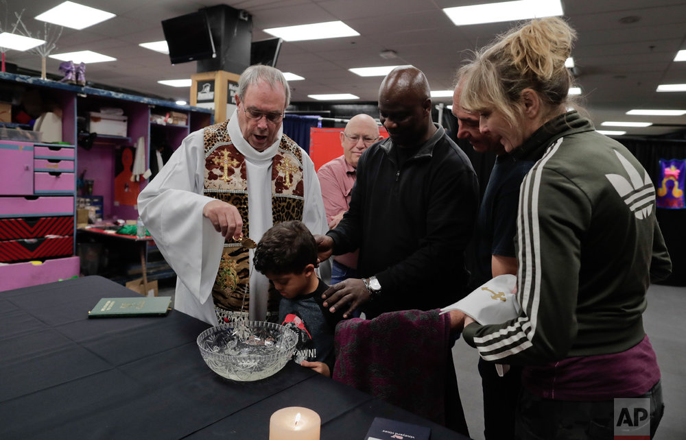 Rev. Jerry Hogan, left, of the U.S. Conference of Catholic Bishops' Circus and Traveling Shows Ministry, leads a baptism service for 6-year-old Eddie Strickland, the son of Jimmie Strickland, a member of the crew before a Ringling Bros. circus show at the Dunkin Donuts Center, Thursday, May 4, 2017, in Providence, R.I. Hogan's vestments were made by the costume department from old elephant blankets. (AP Photo/Julie Jacobson)