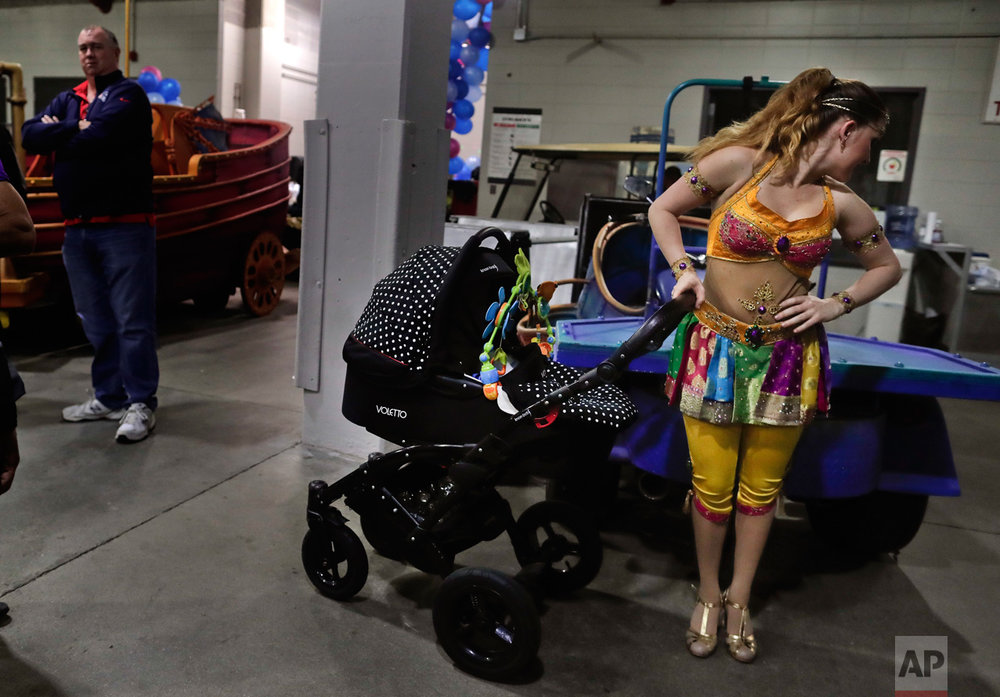 Ringling Bros. high wire performer Anna Lebedeva stands next to her 3-month-old son, Amir, in his stroller while waiting to go on for the show's finale, Friday, May 5, 2017, in Providence, R.I. Lebedeva and her husband, fellow performer Mustafa Danguir, dream of starting their own show, or maybe opening a circus school in Morocco to teach future generations. They're optimistic something good will come along. (AP Photo/Julie Jacobson)