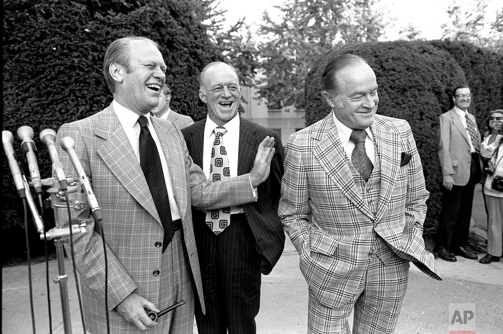 President Gerald Ford laughs at a joke from Bob Hope about their golf game Saturday evening, October 5, 1974, as they talked with newsmen outside Bethesda Naval Hospital prior to visiting First Lady Betty Ford.  Standing in the background is Hugh Davis, a friend of Hope's. (AP Photo)