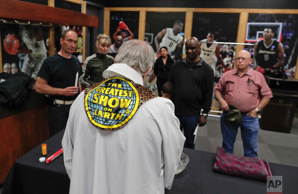 Rev. Jerry Hogan, of the U.S. Conference of Catholic Bishops' Circus and Traveling Shows Ministry, leads a baptism service for the son of a member of the crew before a Ringling Bros. circus show at the Dunkin Donuts Center, Thursday, May 4, 2017, in Providence, R.I. Hogan's vestments were made by the costume department from old elephant blankets. (AP Photo/Julie Jacobson)