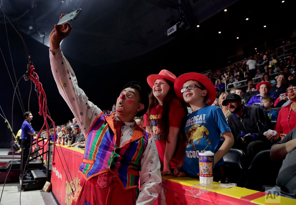 "Ringling Bros. clown Ivan Skinfill poses for a selfie photo with children during the intermission of a show, Thursday, May 4, 2017, in Providence, R.I. ""The Greatest Show on Earth"" is about to put on its last show on earth. For the performers who travel with the Ringling Bros. and Barnum & Bailey Circus, its demise means the end of a unique way of life for hundreds of performers and crew members. (AP Photo/Julie Jacobson)"