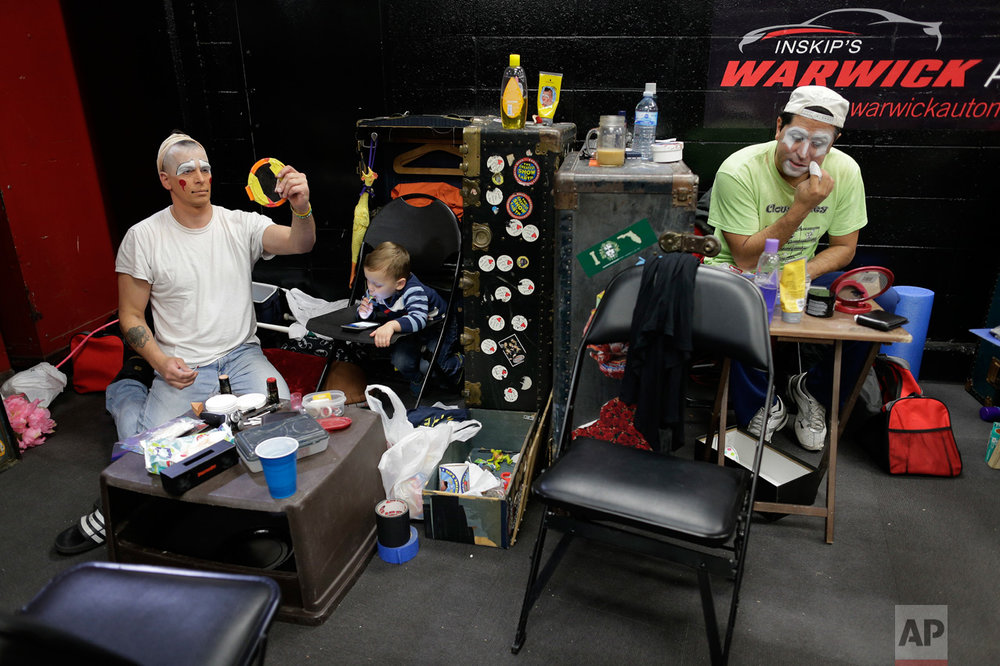 "Ringling Bros. boss clown Sandor Eke, left, and Ivan Vargas put on makeup as Eke's 2-year-old son Michael watches videos on a phone before a performance, Friday, May 5, 2017, in Providence, R.I. ""The Greatest Show on Earth"" is about to put on its last show on earth. For the performers who travel with the Ringling Bros. and Barnum & Bailey Circus, its demise means the end of a unique way of life for hundreds of performers and crew members. (AP Photo/Julie Jacobson)"