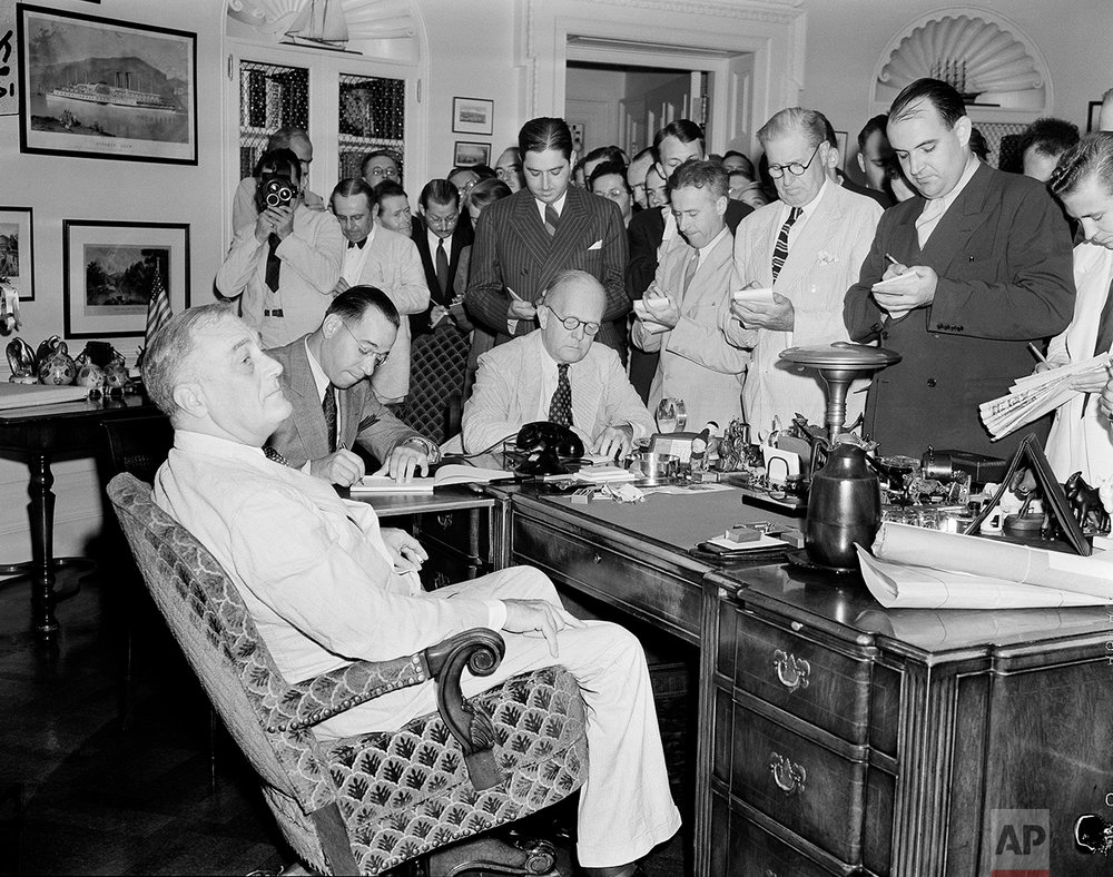White House reporters, straining to hear every word, crowd around the desk of President Franklin D. Roosevelt in the executive office in Washington, D.C., Aug. 25, 1939, to hear the president say that he did not regard the present European situation as certain to result in war. This is the first time a cameraman (left, background) has been allowed in a presidential press conference since Roosevelt's first conference in 1933. The president leans back in swivel chair. Behind him is Henry Kannee, secretary to the presidential secretary Edwin Watson, taking presidential record of the conversation.  (AP Photo/Henry Griffin)