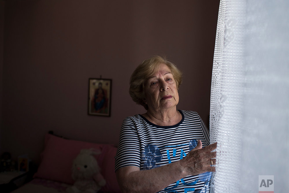 In this Monday, May 15, 2017 photo, Greek pensioner Mina Griva, 78, a widow and former factory worker in Germany, poses in her home in Athens.  (AP Photo/Petros Giannakouris)