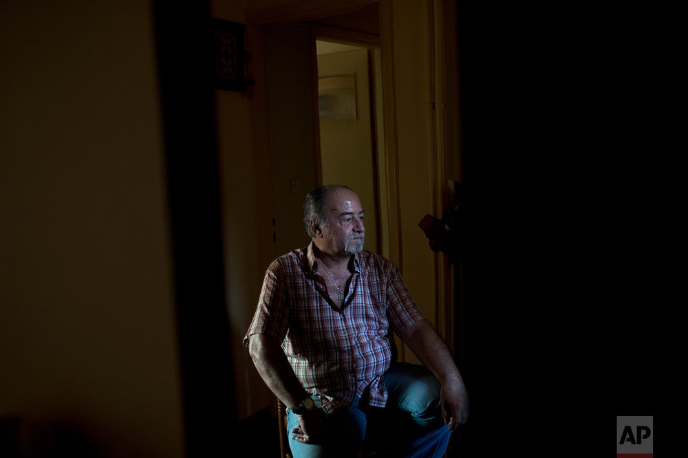 "In this Monday, May 15, 2017 photo, Greek pensioner Fotis Milas, 66, a former paper factory employee, sits in his small apartment in Athens. The new austerity measures are likely to cut his pension to about 800 euros, Milas said. ""I will start having a very, very hard time. At the moment, thank God, I'm not hungry. For now."" (AP Photo/Petros Giannakouris)"