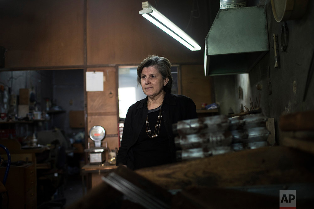 "In this Thursday, May 11, 2017 photo, Greek pensioner Paraskevi Koliambi, 60, a widow and former silversmith, poses during a visit to her son's workshop in Athens. ""I see it as uncertain, the future,"" Koliambi said. ""We're trying to hold on. My son is really fighting to keep the business.... Whatever we had set aside is all gone _ on taxes."" (AP Photo/Petros Giannakouris)"