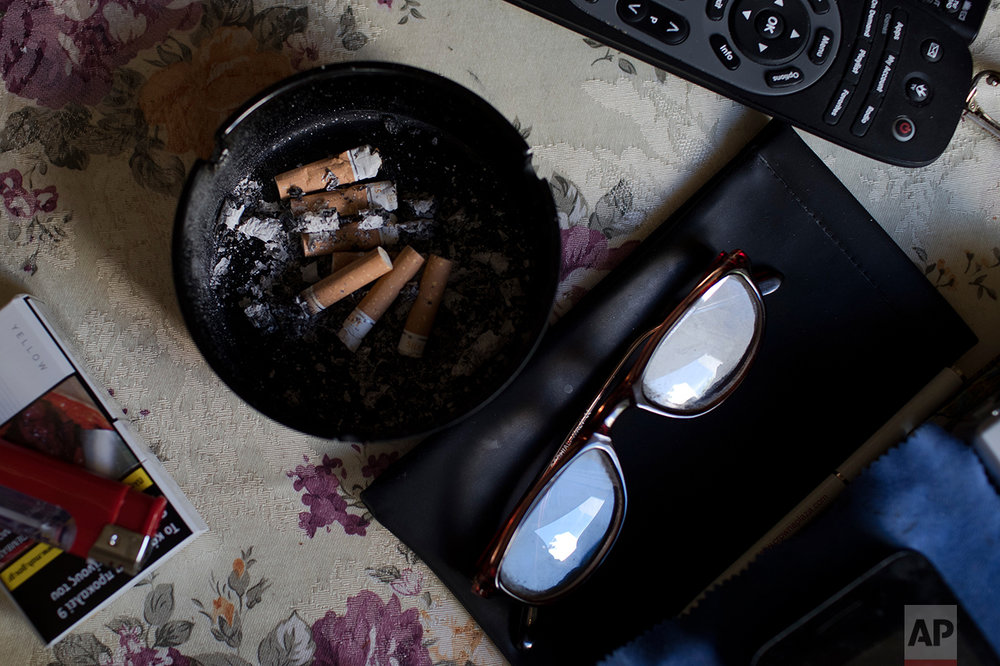 "In this Monday, May 15, 2017 photo, an ashtray, a pair of glasses and a TV remote control sit on a table in the small apartment of Greek pensioner Fotis Milas, 66, a former paper factory employee in Athens. The new austerity measures are likely to cut his pension to about 800 euros, Milas said. ""I will start having a very, very hard time. At the moment, thank God, I'm not hungry. For now."" (AP Photo/Petros Giannakouris)"
