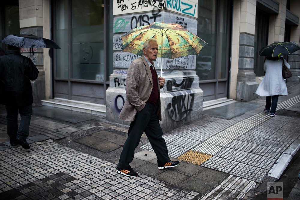 In this Thursday, May 18, 2017 photo an elderly man holding an umbrella walks during rainfall in central Athens. (AP Photo/Petros Giannakouris)