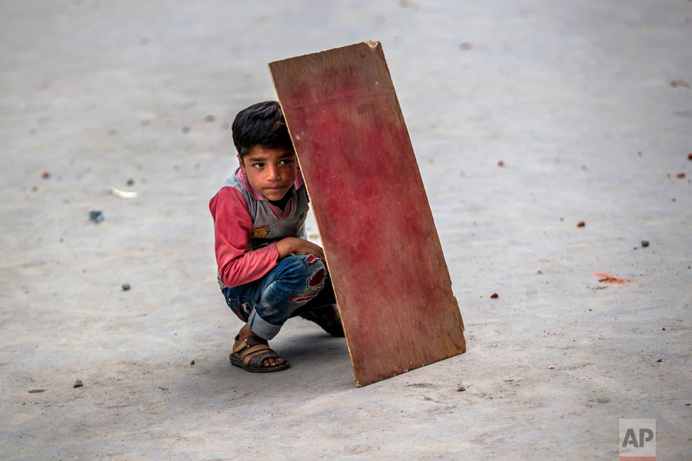 A Kashmiri boy hides behind a piece of plywood to shield himself from stones and glass marbles during a clash between Indian police and protesters during a protest in Srinagar, Indian controlled Kashmir, Friday, May 19, 2017. Separatist leaders called for a protest against the detention of female separatist leader Asiya Adrabi, chairman of Dukhtaran-e-Millat (Daughters of the Nation). They also demanded the release of all political prisoners from Indian prisons. (AP Photo/Dar Yasin)