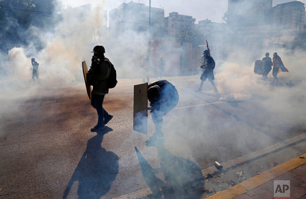 Anti-government protesters shield themselves from tear gas canisters as security forces disperse an opposition march and block them from reaching the Interior Ministry in Caracas, Venezuela, on Thursday, May 18, 2017. Venezuela has reached almost two months of anti-government unrest in which more than 40 people have been killed. (AP Photo/Ariana Cubillos)