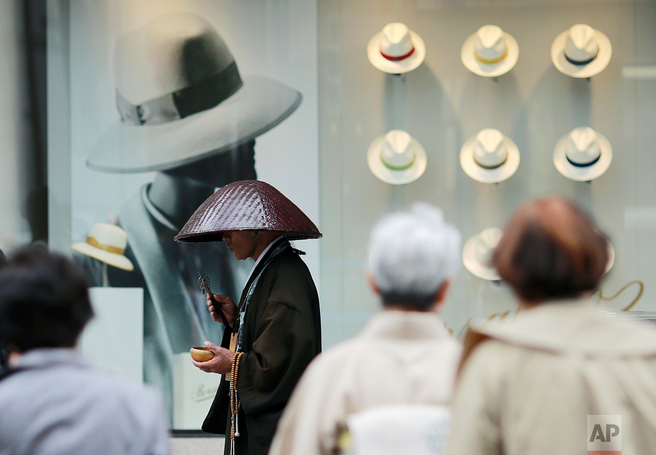 A Buddhist monk offers prayers in front of a window display of hats at a department store in the Ginza shopping district in Tokyo Tuesday, May 16, 2017. (AP Photo/Eugene Hoshiko)