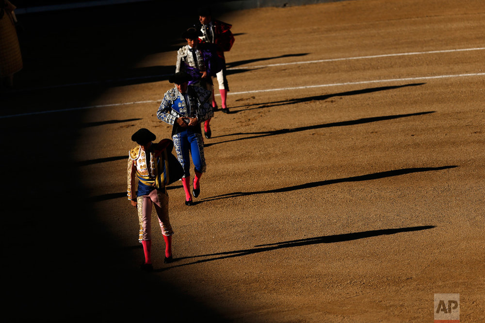 """Bullfighters and assistants walk along the ring during the """"paseillo"""" (ritual entrance) to the arena before a bullfight at the Las Ventas bullring in Madrid, Thursday, May 18, 2017. (AP Photo/Francisco Seco)"""