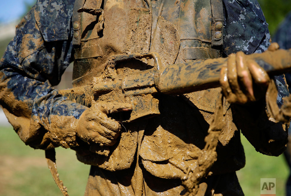 """A first-year midshipman, known as a """"plebe,"""" carries a dummy rifle covered in mud during Sea Trials, a day-long training exercise that caps off their plebe year at the U.S. Naval Academy in Annapolis, Md., Tuesday, May 16, 2017. (AP Photo/Patrick Semansky)"""