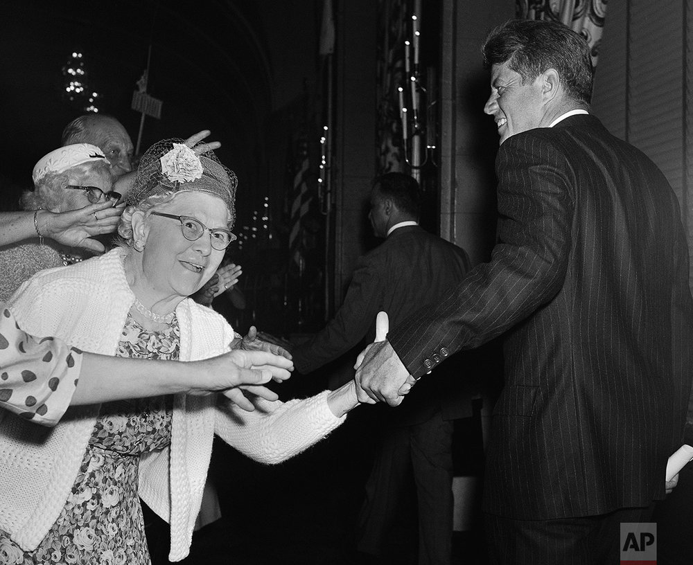 """Reaching hands engulf President John Kennedy's right hand and coat sleeve June 13, 1963 after he addressed a meeting in Washington of the National Council of Senior Citizens.     Kennedy  told the council that """"it's time the United States caught up"""" with all the nations of  Western Europe and provided medical and hospital care for its elderly people. (AP Photo/Bill Allen)"""