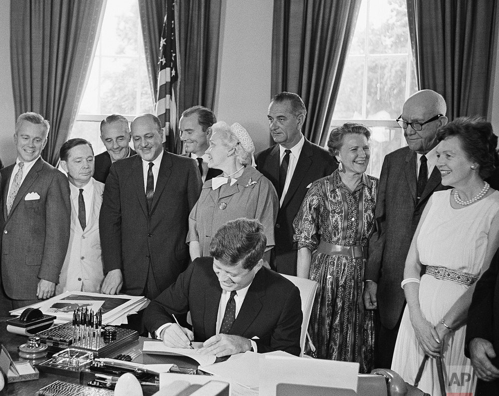 President John F. Kennedy signs a new housing bill June 30, 1961 at the White House. Attending the ceremonies are, from left; Rep. Carl Albert, D-Okla, ; Mayor Richardson Dilworth of Philadelphia; Housing Administrator Robert Weaver; Jack Conway, deputy housing administrator; Mrs. Marie McGuire, Public Housing Administration commissionar, and Vice President Lyndon Johnson. All others are unidentified. (AP Photo/Bob Schutz)