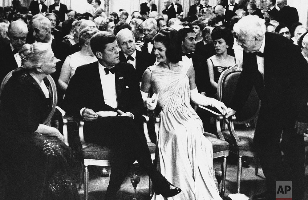 In this April 30, 1962 photo, President John F. Kennedy, sitting with his wife Jacqueline, looks on as poet Robert Frost, right, and Mrs. Richard J. Walsh (Pearl Buck) exchange greetings in the East Room of the White House in Washington. The first family and their guests are gathered in the East Room to hear a dramatic reading by actor Fredric March after a dinner honoring winners of the Nobel Prize. (AP Photo)