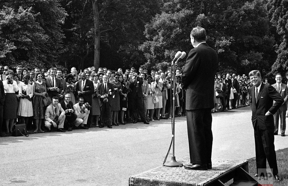 Sen. Hubert Humphrey (D-Minn.), addresses approximately 300 students at the White House in Washington on June 22, 1962, as President John F. Kennedy listens. The students who are going to Africa under the sponsorship of Operation Crossroads Africa, met with the chief executive, Humphrey, and Dr. James Robinson, right, of New York City, in the Rose Garden. Operation Crossroads Africa is privately financed, interracial, nondenominational organization. (AP Photo/Henry Burroughs)