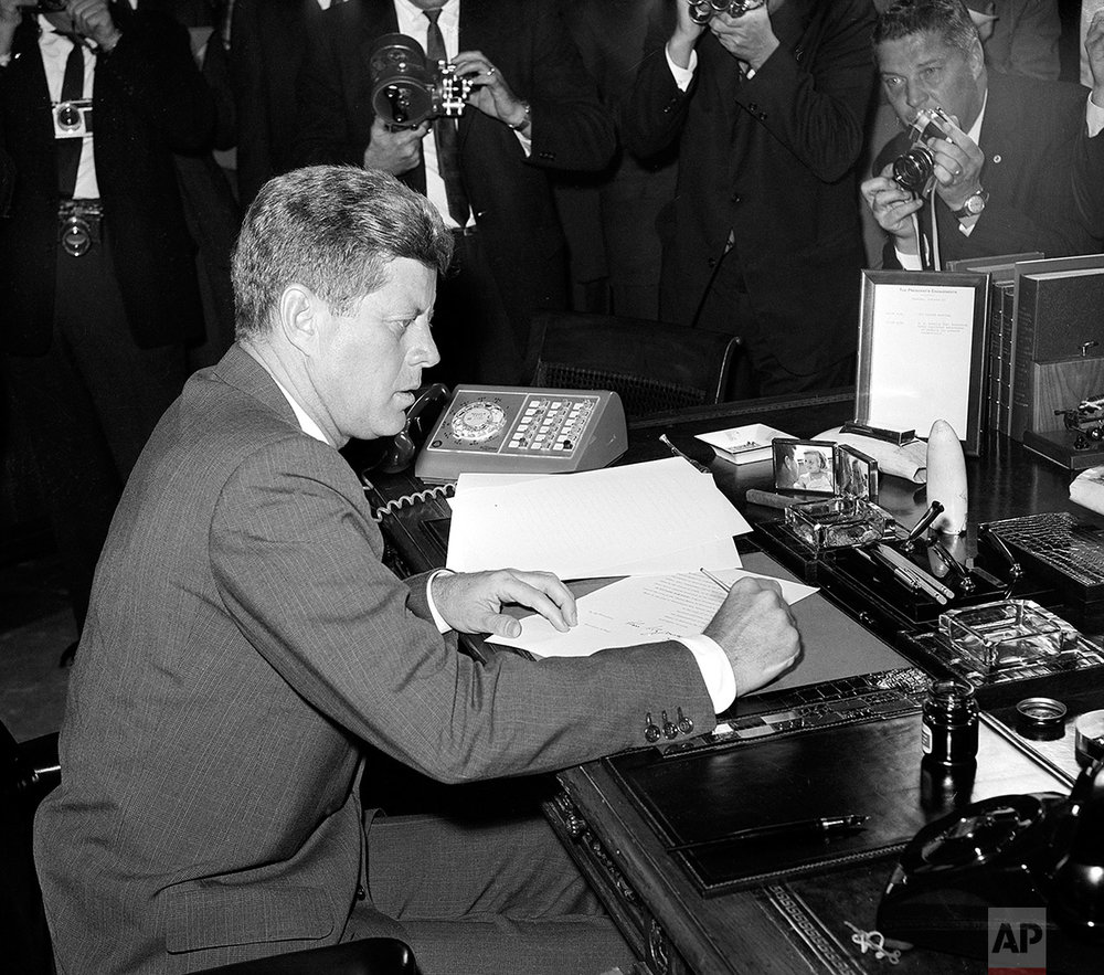 U.S. President John F. Kennedy is surrounded by photographers, as he sits at his desk in the White House, in Washington, D.C., on October 23, 1962, shortly after signing a presidential proclamation concerning the Cuba crisis. (AP Photo)