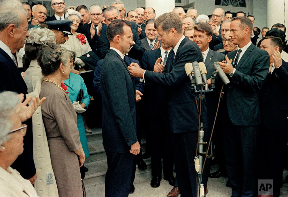 U. S. President John F. Kennedy, right, shakes hands with Astronaut Gordon Cooper at the White House during a reception, May 21, 1963. Gordon Cooper  performed the last Mercury mission and completed 22 orbits in Faith 7 to evaluate effects of one day in space, May 15–16, 1963. Others unidentified. (AP Photo)