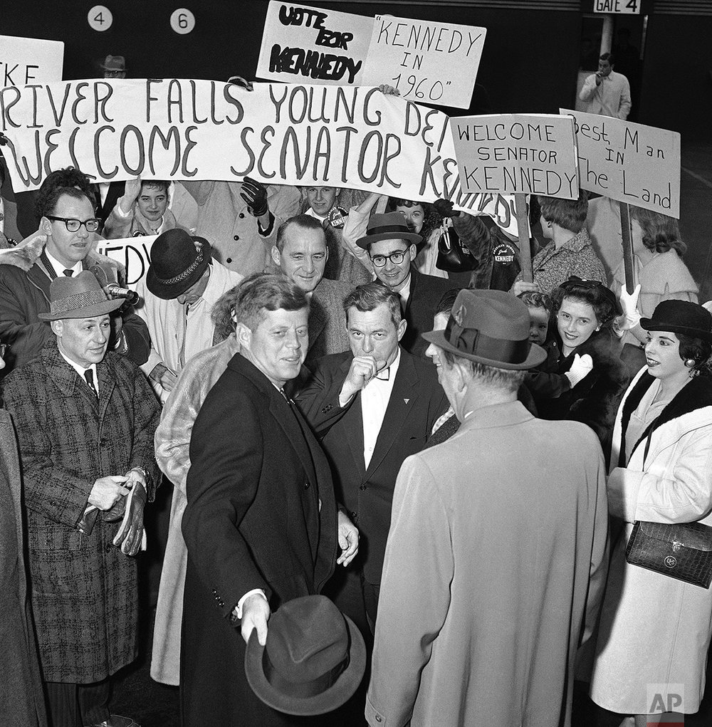 Sen. John Kennedy of Massachusetts (center, foreground) is greeted by students and state political leaders as he arrives in Minneapolis, Nov. 12, 1959 to begin a two-day tour of Minnesota and Wisconsin. Since 1956, Kennedy has criss-crossed the nation, visiting all 50 states. (AP Photo/Gene Herrick)