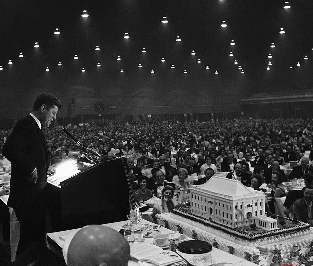 President Kennedy smiles as he delivers a joking remark to the 6,000 attending the $100-a-plate Democratic dinner on May 27, 1961 in Washington's National Guard Armory, to help him celebrate his 44th birthday. The event was held in advance of the actual date of May 29, at which time the President will not be in Washington. The cake in foreground weights 1½ tons and is topped by a replica of the White House. Funds raised by the dinner went to the Democratic Party campaign fund which is in the red. (AP Photo/Henry Griffin)