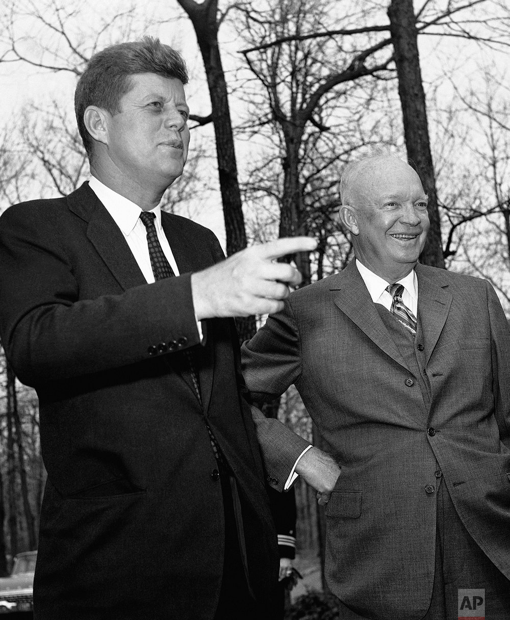 President John Kennedy points as former President Dwight Eisenhower looks out over Camp David after the two conferred on April 22, 1961 at the presidential hideaway at Thurmont, Maryland on the Cuban situation. (AP Photo)