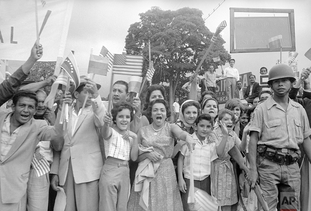 Crowd greets Venezuela's President Betancourt and U.S. President John F. Kennedy as they ride from airport into city of Caracas, Venezuela on Dec. 16, 1961. (AP Photo)
