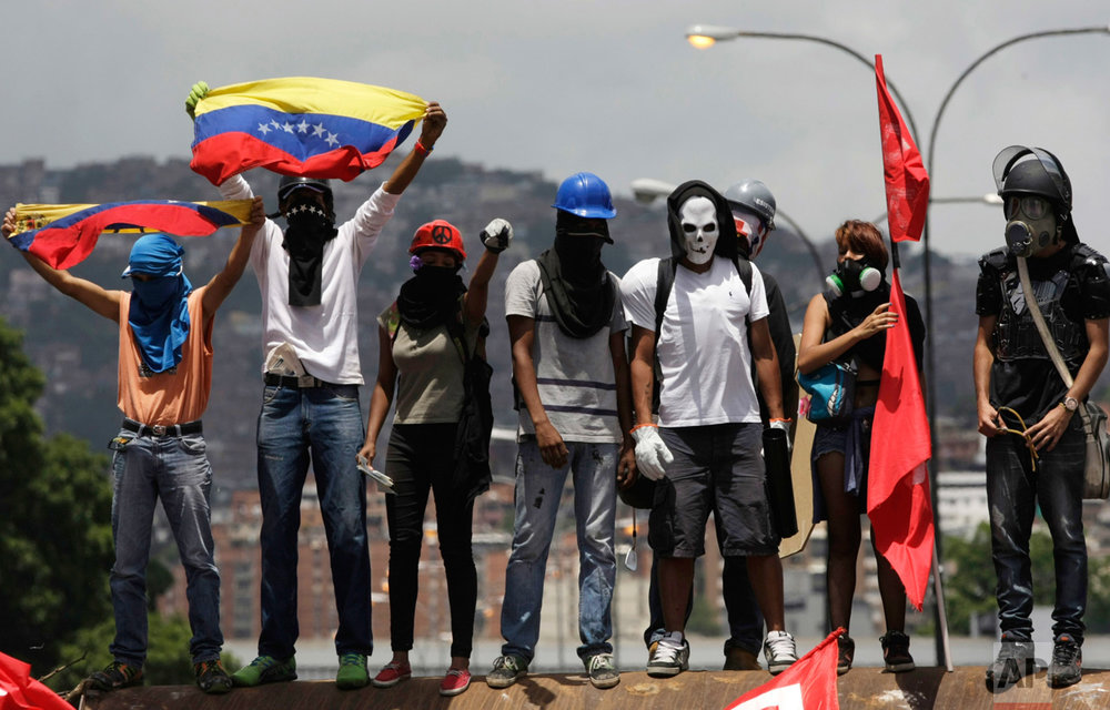 Opponents of President Nicolas Maduro gather to block a major highway in Caracas, Venezuela, Saturday, May 20, 2017. The anti-government protesters took to the streets again after weeks of unrest have left more than 40 dead. (AP Photo/Fernando Llano)