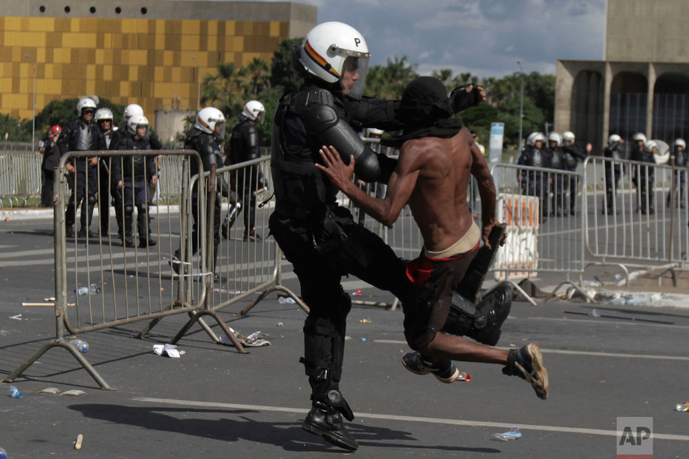 A demonstrator clashes with a police officer during an anti-government protest in Brasilia, Brazil, Wednesday, May 24, 2017. Brazil's president ordered federal troops to restore order in the country's capital following the evacuation of some ministries during clashes between police and protesters who are seeking the leader's ouster. Protesters demanded President Michel Temer's removal amid allegations against him of corruption. (AP Photo/Eraldo Peres)
