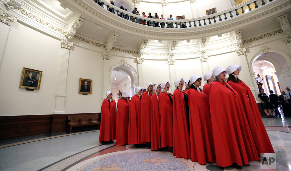 "Activists dressed as characters from ""The Handmaid's Tale"" chant in the Texas Capitol Rotunda as they protest SB8, a bill that would require health care facilities, including hospitals and abortion clinics, to bury or cremate any fetal remains whether from abortion, miscarriage or stillbirth, and they would be banned from donating aborted fetal tissue to medical researchers, Tuesday, May 23, 2017, in Austin. (AP Photo/Eric Gay)"