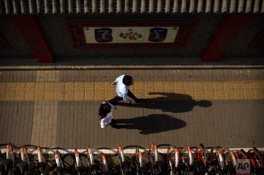 Pedestrians cast shadows as they walk along a sidewalk in Beijing, Thursday, May 25, 2017. (AP Photo/Mark Schiefelbein)