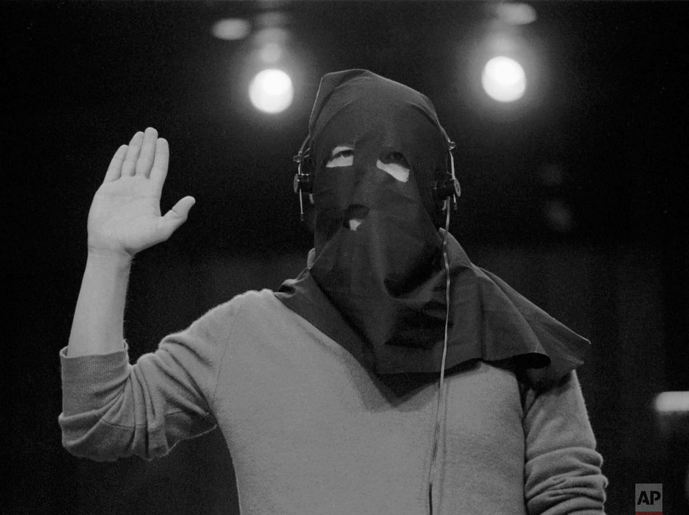Floyd Carlton is shielded by a hood to conceal his face while being sworn in as a witness before a Senate Foreign Relations subcommittee on Capitol Hill Feb.10, 1988. Carlton is described by investigators as a former pilot for Panamanian military ruler Gen. Manuel Antonio Noriega, who is being investigated by the subcommittee. (AP Photo/ John Duricka)