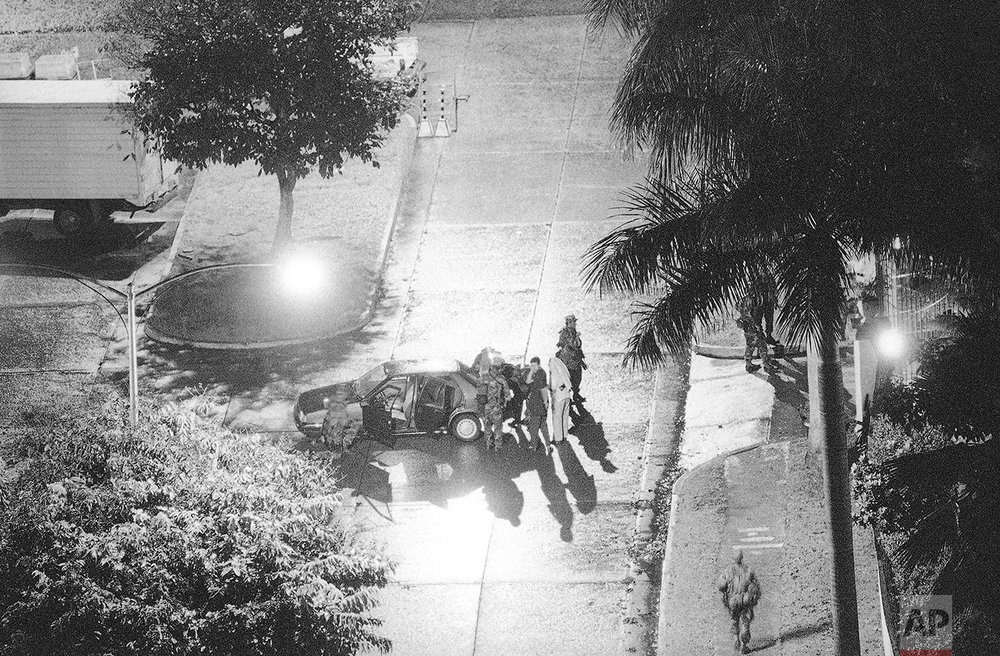 American soldiers search a car leaving the Vatican Embassy in Panama City, Dec. 27, 1989. Manuel Noriega turned himself in earlier to the Papal Nuncio and requested asylum, setting off a diplomatic standoff in Panama City. (AP Photo/John Hopper)