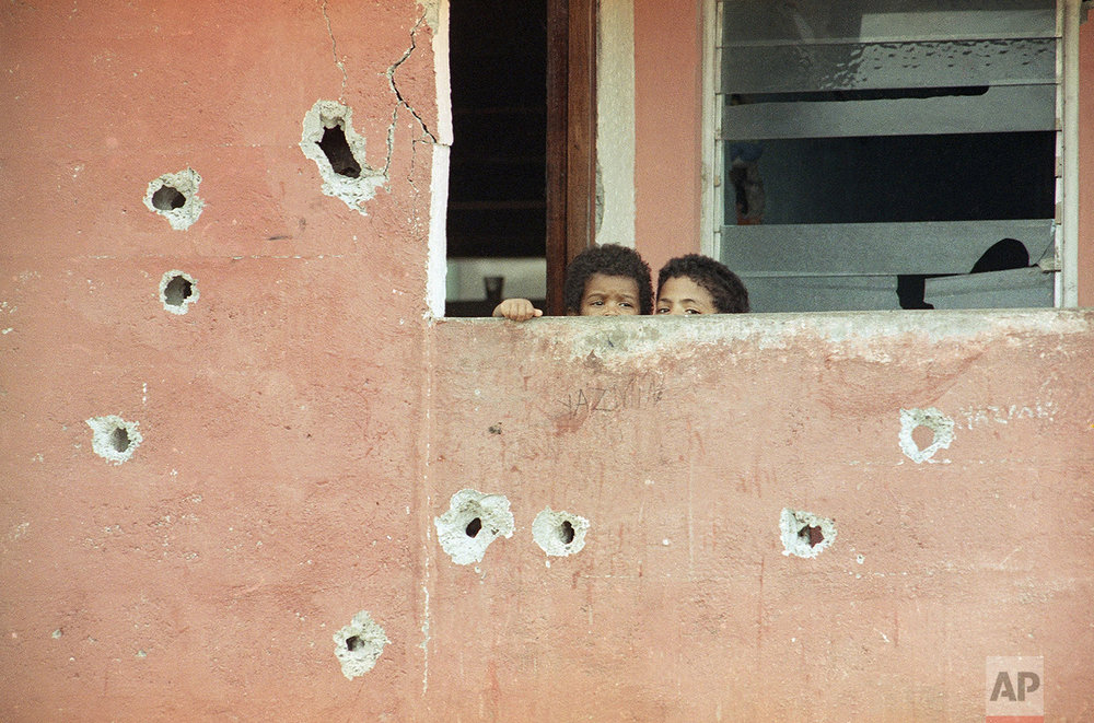 Youngsters peer from a bullet pocked balcony in the devastated El Chorillo barrio section of Panama City, Thursday, Jan. 4, 1990 on the morning after Manuel Noriega surrendered to American authorities. (AP Photo/John Gaps)