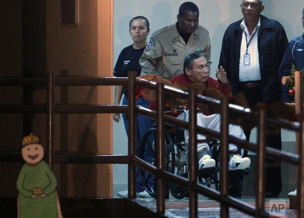In this Dec. 11, 2011 photo, Panama's ex-dictator Manuel Noriega is wheeled in by a police officer inside El Renacer prison in the outskirts of Panama City. Noriega, a onetime U.S. ally who was ousted by an American invasion in 1989, died late Monday, May 29, 2017, at age 83. (AP Photo/Esteban Felix)