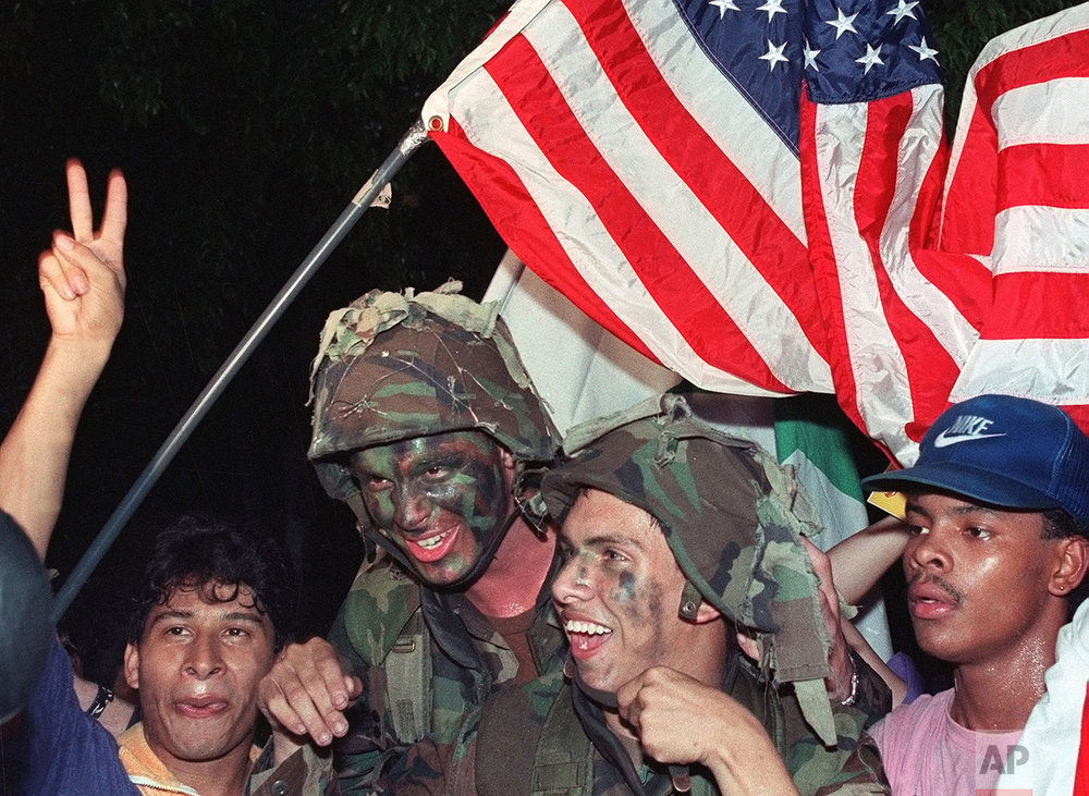 U.S. soldiers carry an American flag through the streets of Panama City as they celebrate with Panamanian citizens in January, 1990 following the surrender of Panamanian strongman Manuel Noriega.  (AP Photo/John Gaps III)
