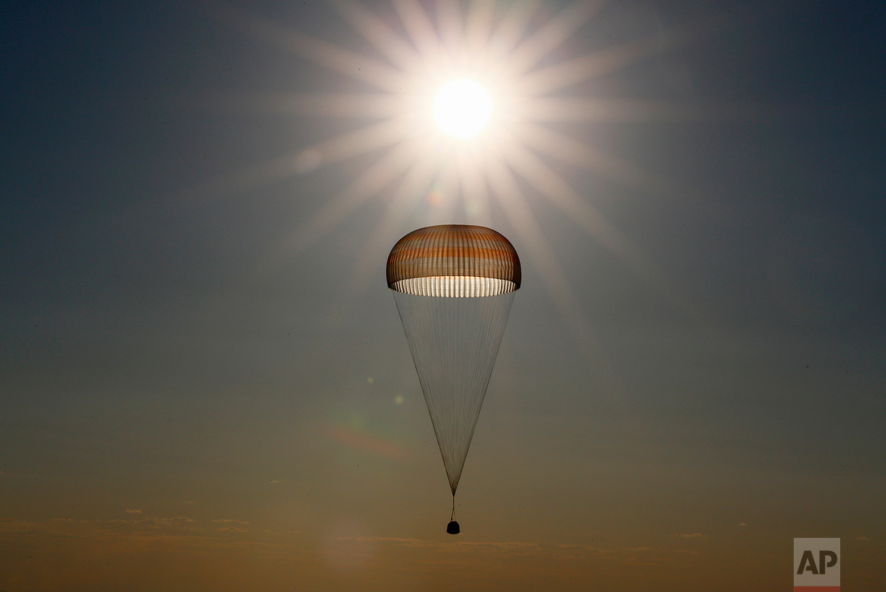 A Russian Soyuz capsule carrying Russian cosmonaut Oleg Novitsky and French astronaut Thomas Pesquet, who spent a half-year aboard the International Space Station, descends by parachute to land in a remote area outside the town of Dzhezkazgan, Kazakhstan, on Friday, June 2, 2017. (Shamil Zhumatov/Pool via AP)