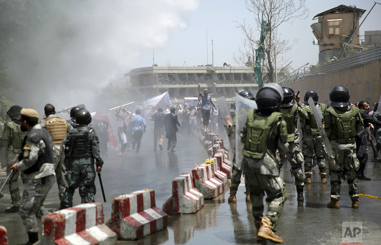Protesters throw stones at police during a demonstration in Kabul, Afghanistan, on Friday, June 2, 2017. Hundreds of demonstrators demanded better security in the Afghan capital in the wake of a powerful truck bomb attack that killed scores of people. (AP Photo/Massoud Hossaini)